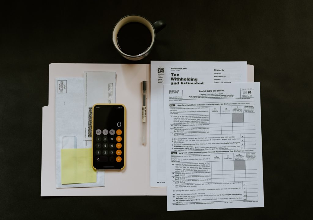 Local Property Tax forms and an iPhone with the calculator open.