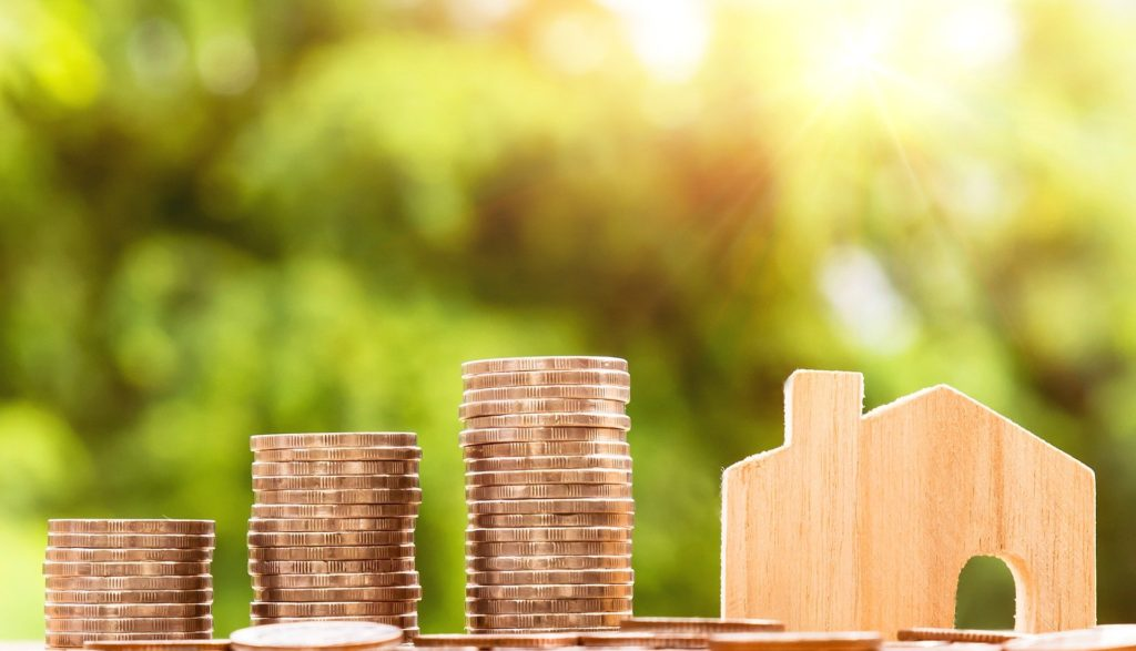 There is a stack of coins and a wooden house. The photo is outdoors. The money is increasing based on the property.