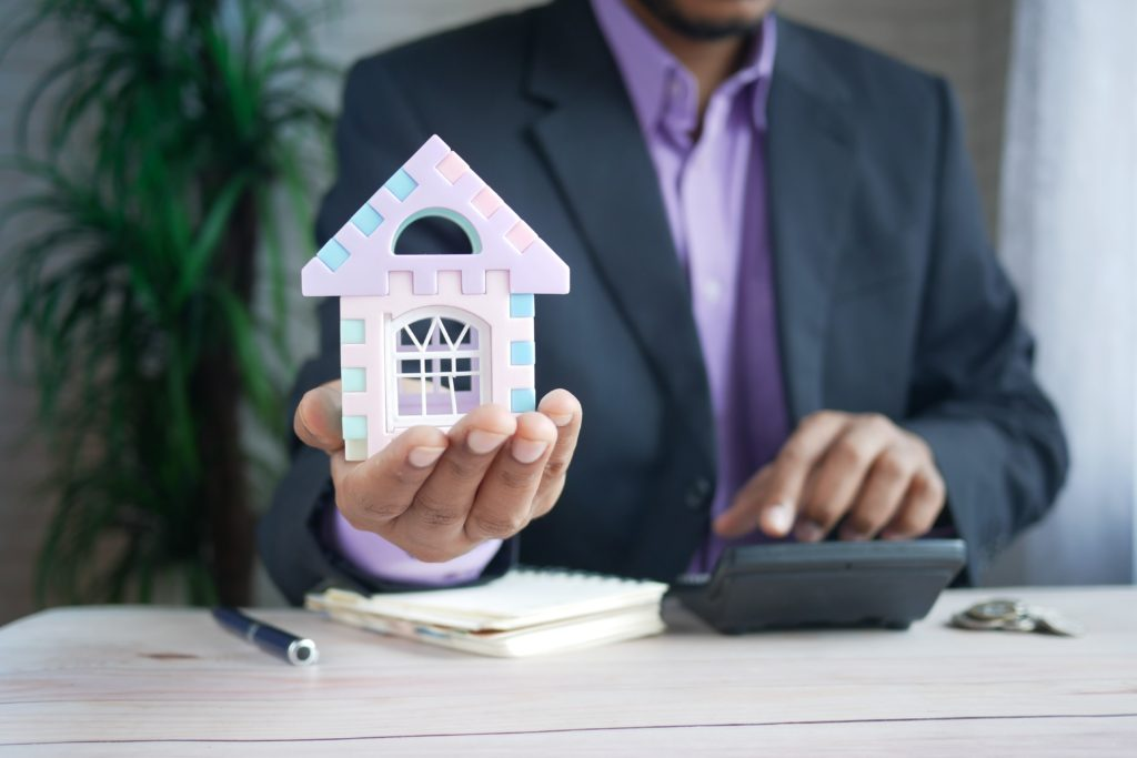 A man holding a small house in his hand and mortgage deeds on the counter with a calculator.